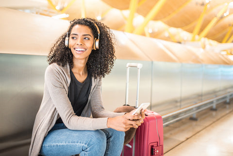 woman with curly natural hair sitting at an airport with luggage