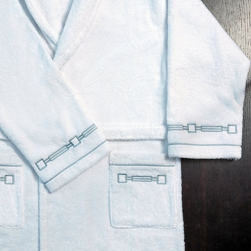 folded white terry bathrobe with retro gray border on arms.