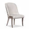 Leland dining chair with light colored fabric and brown legs.