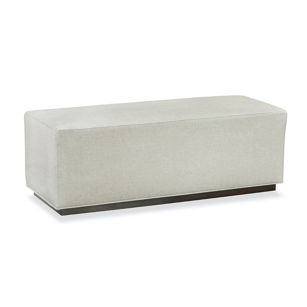 white rectangular bench covered in light colored fabric.