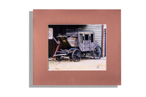 Old buggy near building, matted brown, color photo