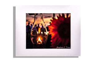 Color photo outdoor party with lantern and flower in forefront, matted white