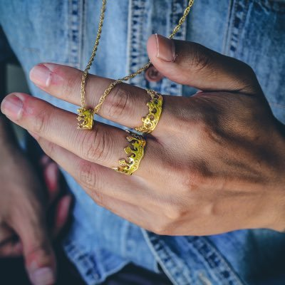 Man wearing crown rings and holding a gold crown necklace in his fingers