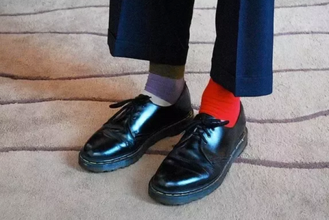 gray and red socks that don't match with dress pants