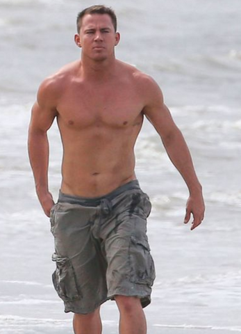 Channing Tatum shirtless on beach with waves in background and cargo shorts