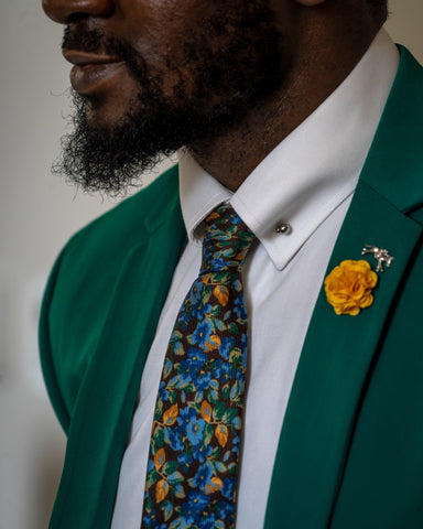 man in green blazer and floral tie