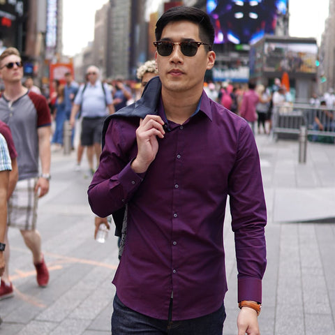man on street with purple dress shirt and black coat