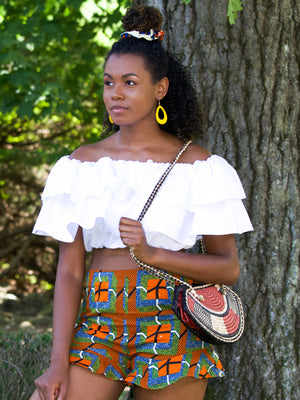 Black model wears high waist shorts with frilled hem. Patter on shorts is a mixture of stripes and squares in orange, black, white, blue and green colours.