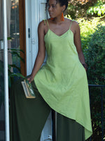 Black model standing in doorway holding a book to her side, wearing lime green  linen tunic with spaghetti straps, gentle v-shaped neckline and long asymmetric hemline.