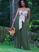 Black model standing, holding a basket of fruit by her side in one hand and other hand in pocket- wearing dark olive green sheer chiffon style trousers. Trousers are a high waist with wide, sheer, floaty legged pants.