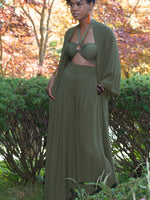 Black model standing with hand in pocket of dark green sheer fabric, wide legged trousers and matching dark olive green full length, open fronted duster. Duster has wide, loose sleeves