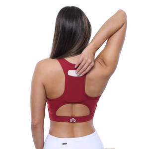Back Side Reaching Phone Pocket View PSYKIE Red Pocket Sports Bra long line sports bra, with built-in phone holder at the back.