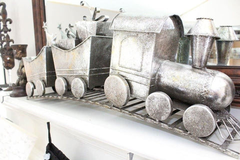 silver christmas train on fireplace mantel