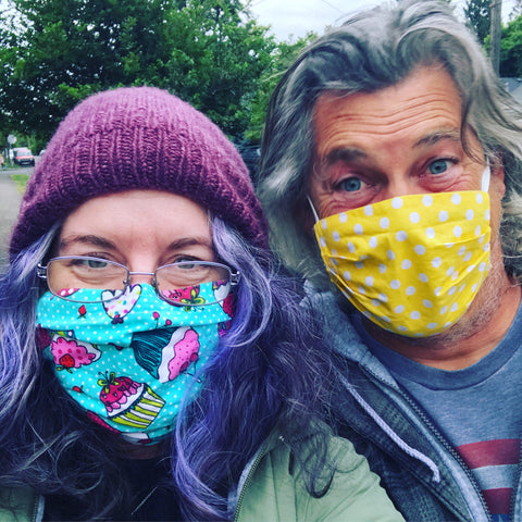 Selfie of two humans in brightly colored masks, with smiling eyes.