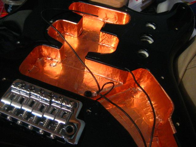 Why is it important to shield guitar electronics?