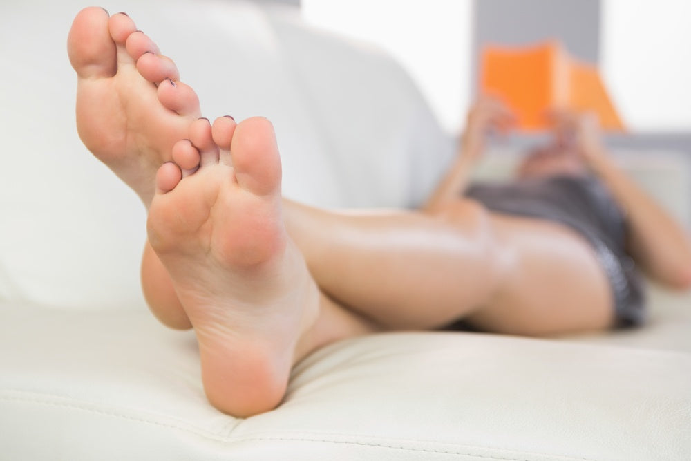 Close up picture of feet from woman lying on couch in bright living room