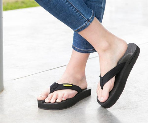 A pair of feet in jeaned pants with exposed ankles wearing The Healing Sole flipflops.