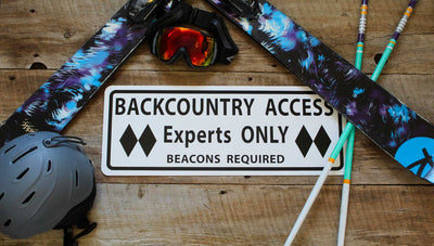 metal sign with black text saying 'backcountry access experts only beacon required' with a white background and various ski gear around the sign