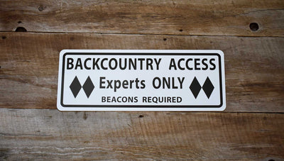 metal sign with black text saying 'backcountry access experts only beacon required' with a white background on a wood background