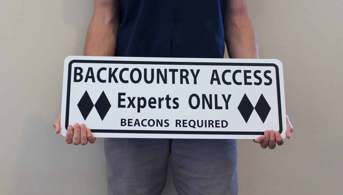 man holding a metal sign with black text saying 'backcountry access experts only beacon required' with a white background