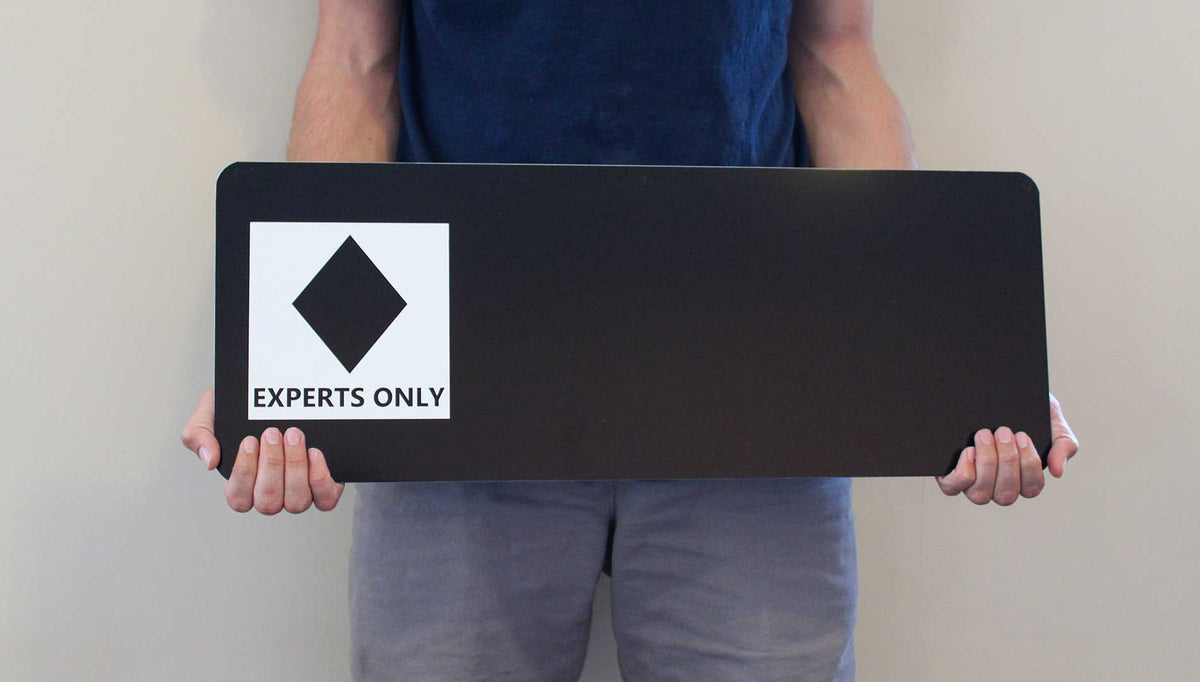 man holding a custom black diamond ski run sign with a black background and white text