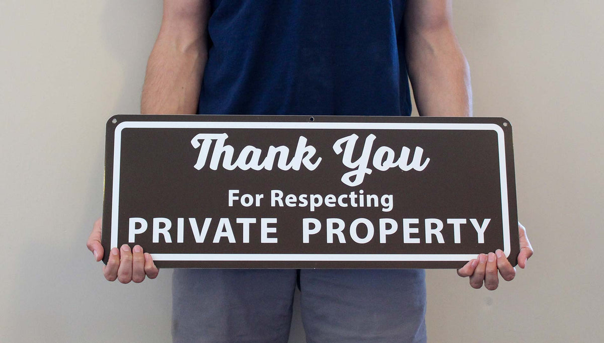 man holding a metal sign that says 'thank you for respecting private property' in white text with a brown background