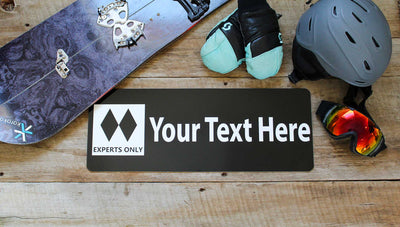 metal ski run sign with a black background and white text that says 'Your Text Here' with two black diamonds surrounded by ski gear