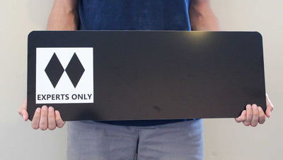 man holding a custom double black diamond ski run sign with a black background and spot for your custom text