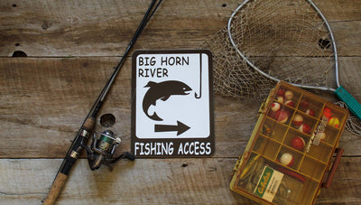 custom metal fishing access sign with fishing gear around the sign and a wooden background