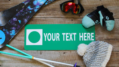 a custom metal green ski run sign with a green background and white text that says 'Your Text Here' with ski gear around the sign