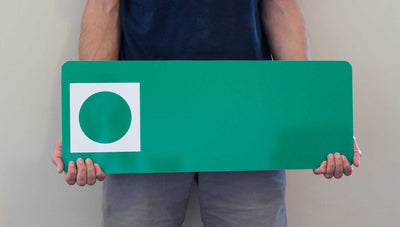a man holding a custom metal green ski run sign with a green background with a spot for your custom text