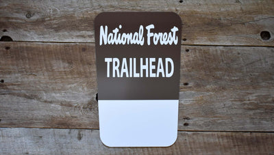 metal sign that says 'national forest trailhead' in white with a brown background with a space for a custom name