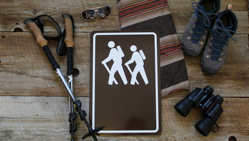 custom hiking trail sign with image of people hiking in white with a brown background and hiking gear around the sign