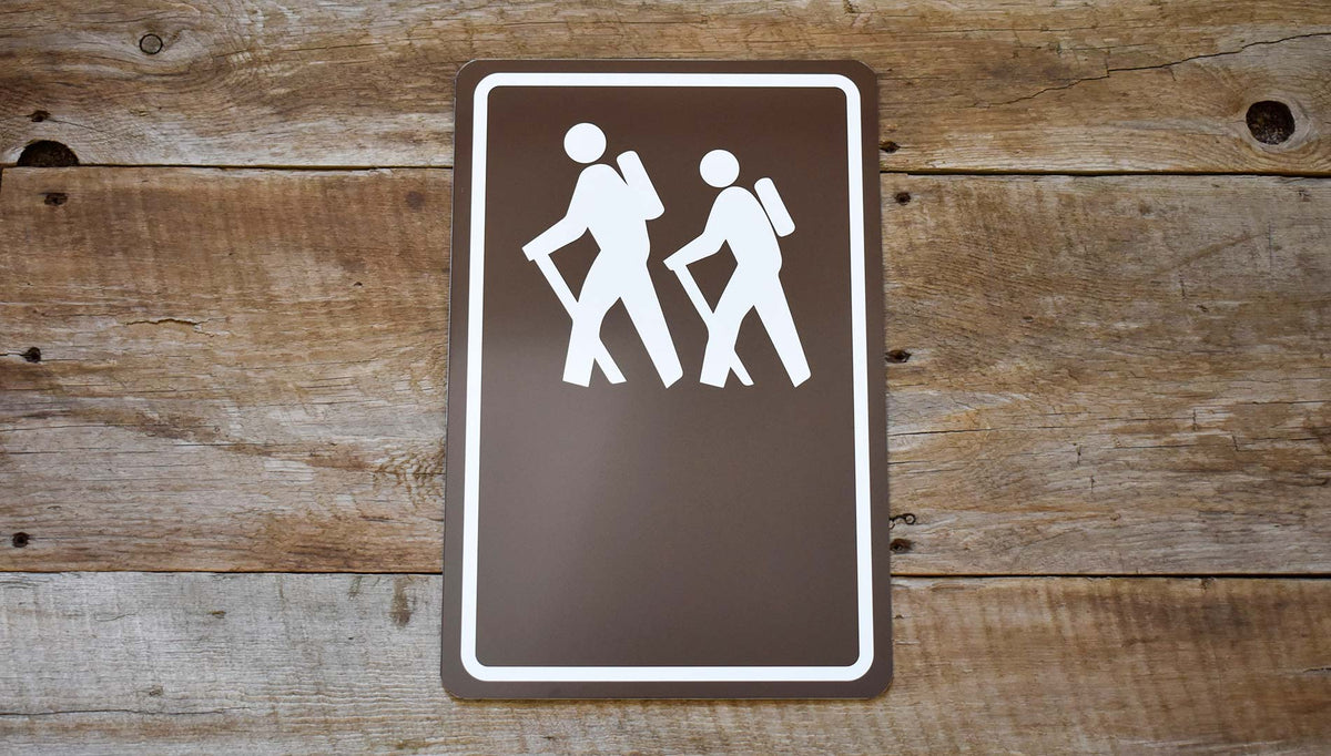 custom hiking trail sign with image of people hiking in white with a brown background