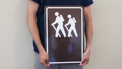 man holding a custom hiking trail sign with image of people hiking in white with a brown background
