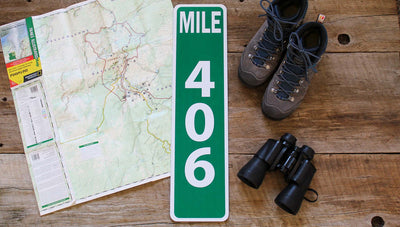 custom metal mile marker sign with a green background and white lettering with travel gear around the sign