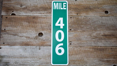 custom metal mile marker sign with a green background and white lettering