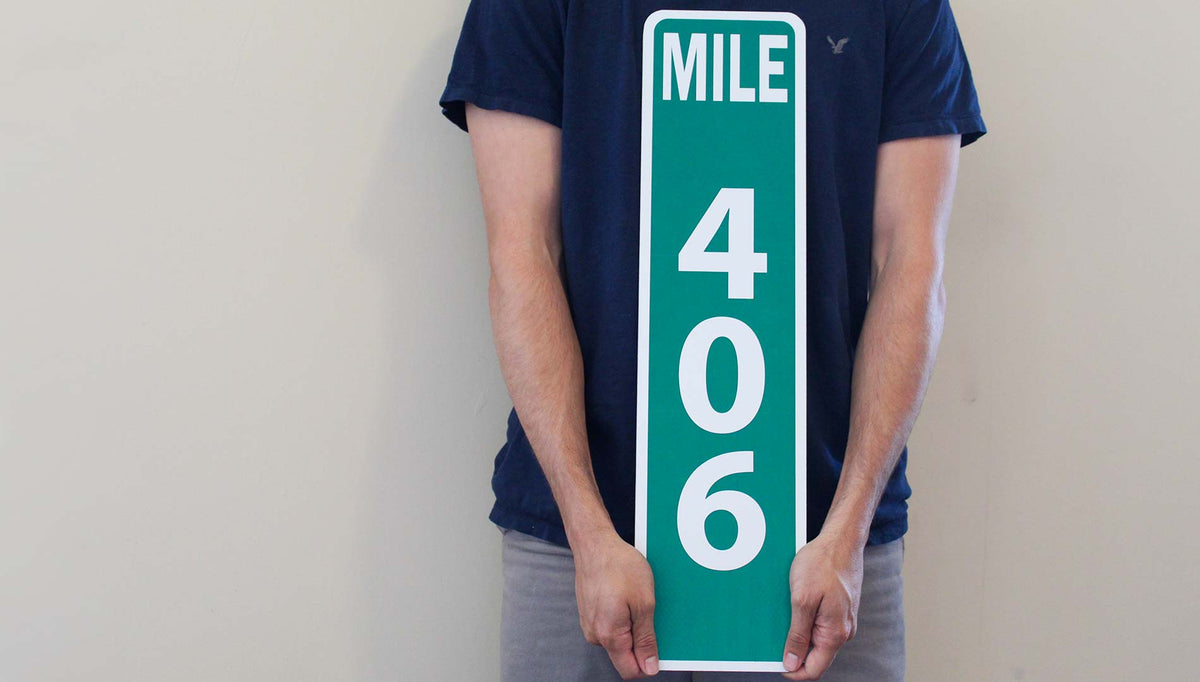 man holding a custom metal mile marker sign with a green background and white lettering