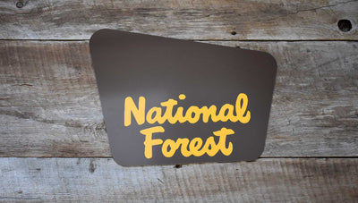 custom national forest sign with a brown background and yellow text that says 'national forest'