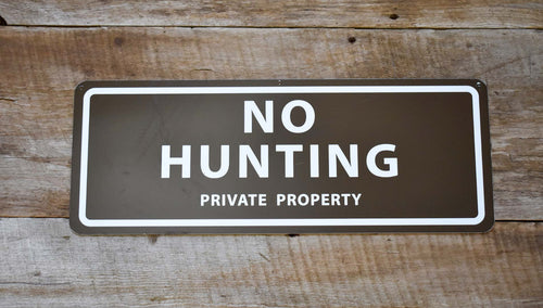 metal sign with a brown background and white text saying 'no hunting private property'