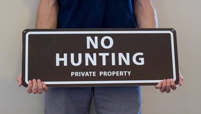 man holding a metal sign with a brown background and white text saying 'no hunting private property'