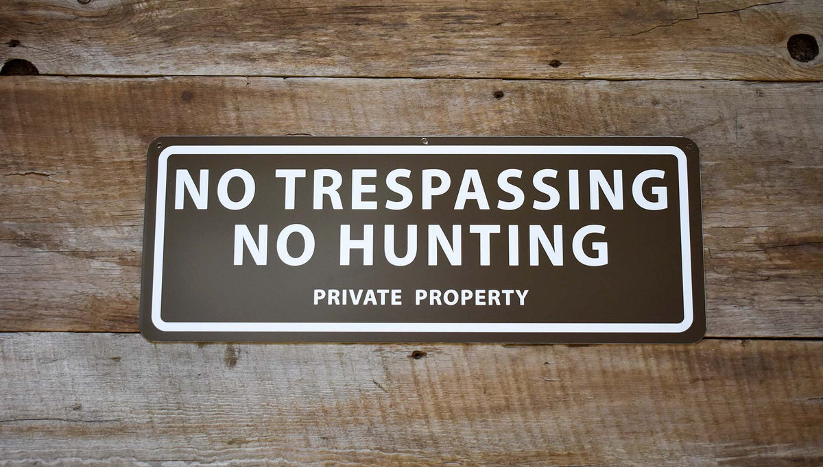 metal sign with a brown background and white text saying 'no trespassing no hunting private property'