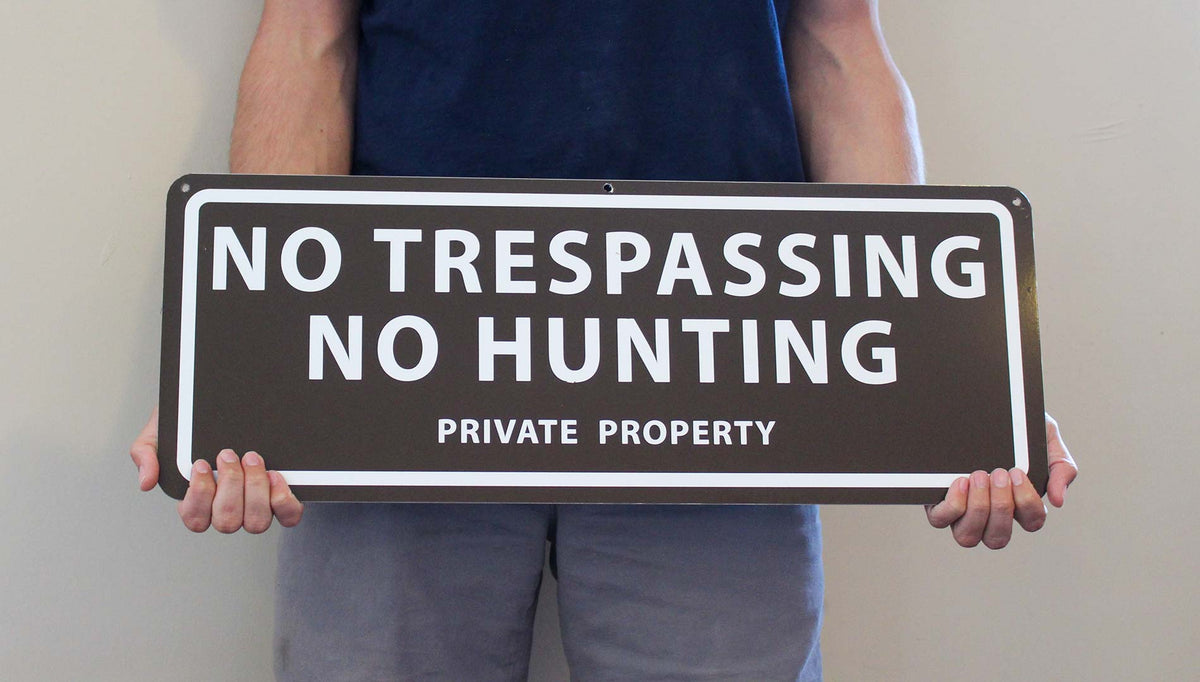 man holding a metal sign with a brown background and white text saying 'no trespassing no hunting private property'