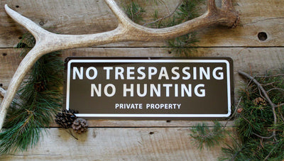metal sign with a brown background and white text saying 'no trespassing no hunting private property' with antlers and pine needles around the sign