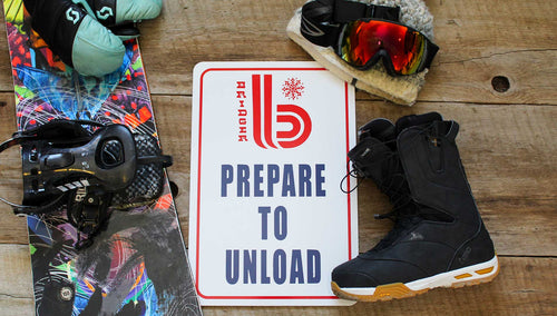 metal sign with white background and a red retro Bridger Bowl logo and 'Prepare to Unload' printed in blue surrounded by ski gear