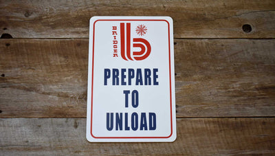 metal sign with white background and a red retro Bridger Bowl logo and 'Prepare to Unload' printed in blue on a wooden backdrop