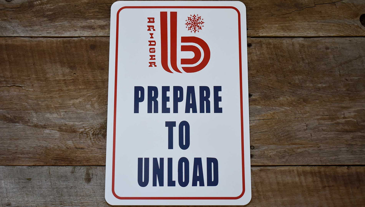 metal sign with white background and a red retro Bridger Bowl logo and 'Prepare to Unload' printed in blue