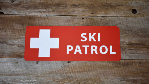 a metal ski patrol sign with a red background and white text that reads 'Ski Patrol' on a wooden background