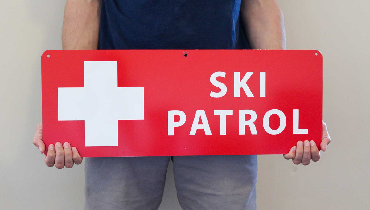 a man holding a metal ski patrol sign with a red background and white text that reads 'Ski Patrol'