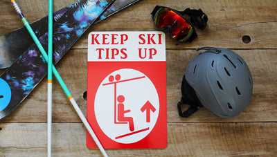 a metal sign with a white background and red text that says 'Keep Ski Tips Up' with an image of a skier on a chairlift surrounded by ski gear